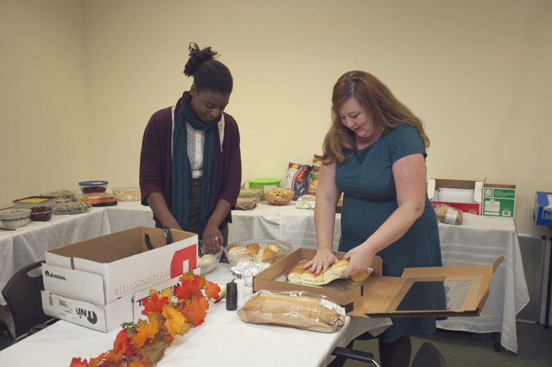 Kenyatta (Reception) and Sarah (Commercial Accounts) in full food-assembly mode